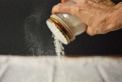 sprinkling flour over the pastry cloth