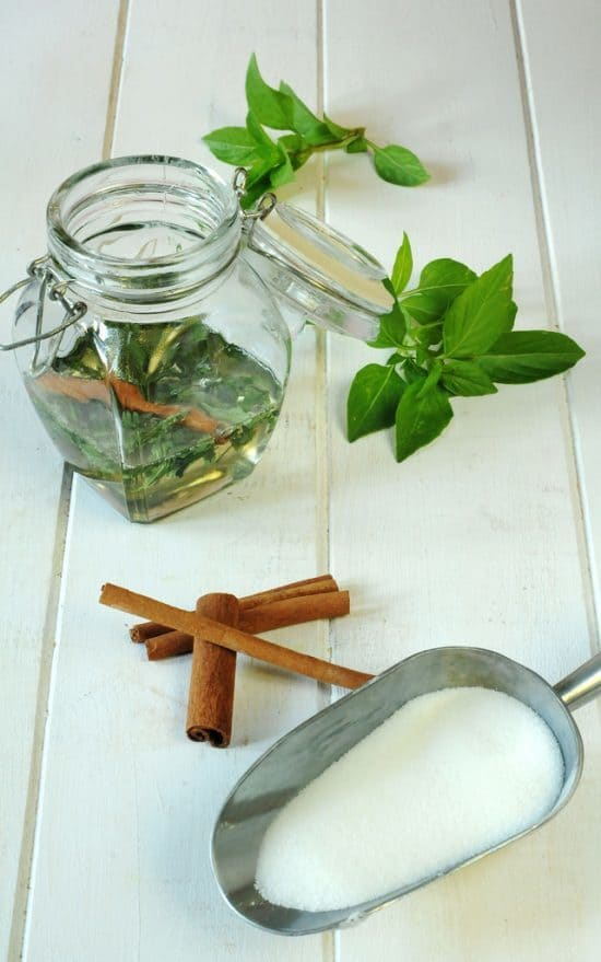 CINNAMON BASIL SYRUP in a jar with cinnamon sticks and sugar in a scoop
