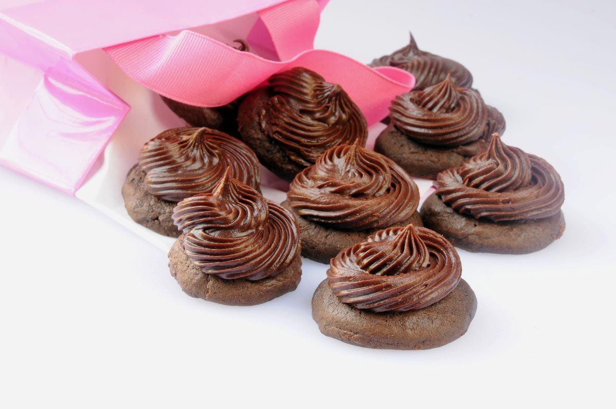 chocolate cupcake tops with a pink bag