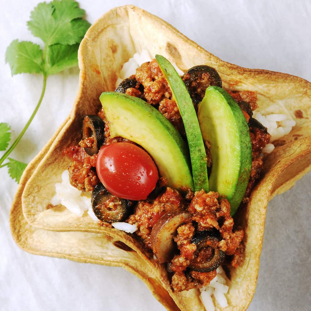 Baked tortilla bowls holding rice, a meat mixture, tomatoes and avocado slices