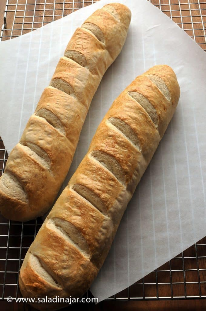 two uncut loaves of French Bread on a cooling rack