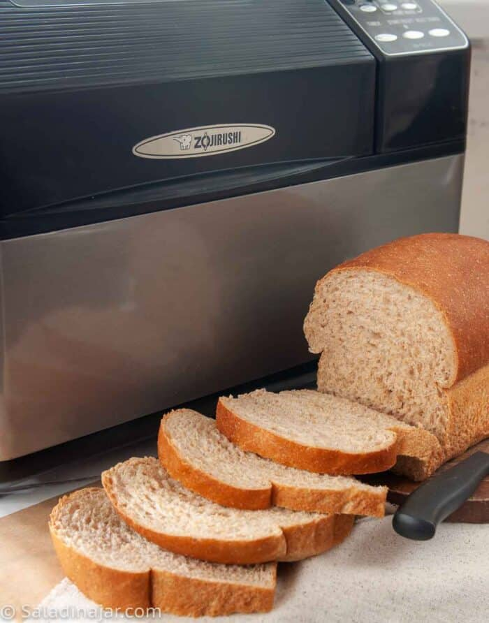 bread machine with sliced Honey Whole Wheat Bread sitting in front of it