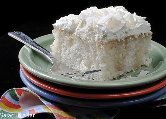 one piece of coconut cake made with a cake mix, drenched with cream of coconut and covered with frozen whipped topping.