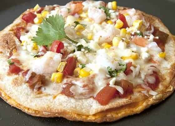 A quick pizza using 2 flour tortillas with cheese between them and other ingredients on top.
