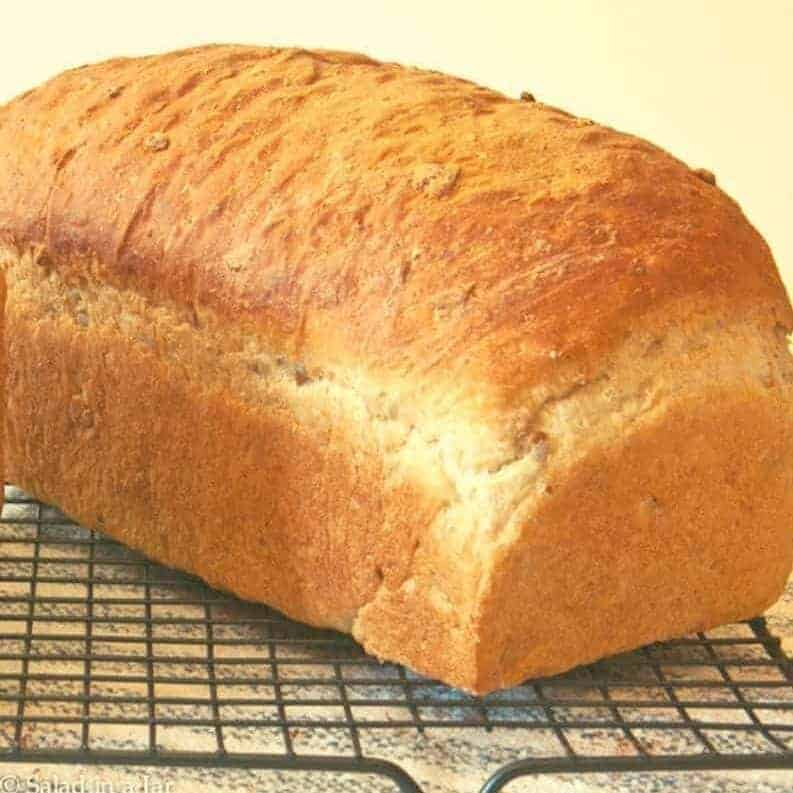 Unsliced loaf of Oatmeal-Sunflower Bread on cooling rack