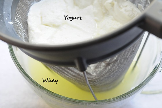 yogurt with whey strained off in bowl below