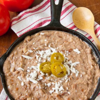 Refried Beans garnished with cheese and jalapeño peppers