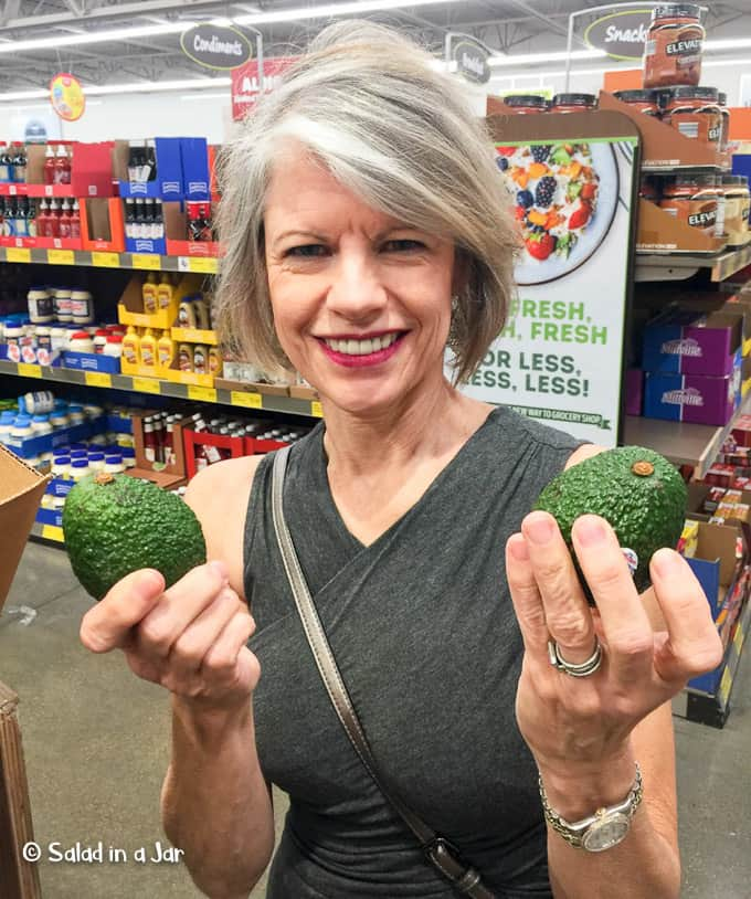woman selecting avocados at the grocery store