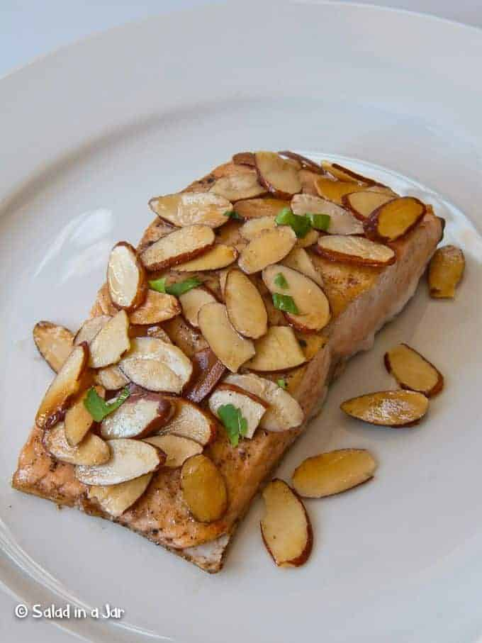 Almond Salmon on a plate covered with toasted almonds