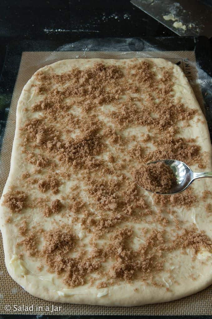 Sprinkling cinnamon-sugar mixture on dough
