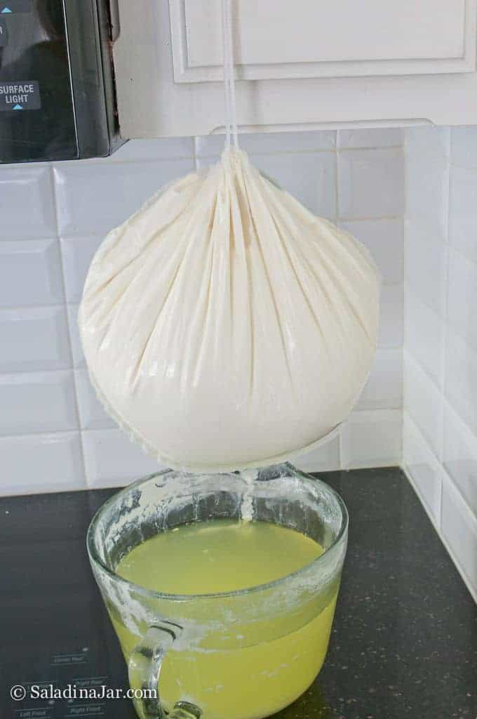 Pouch full of yogurt straining into a 4 qt container.
