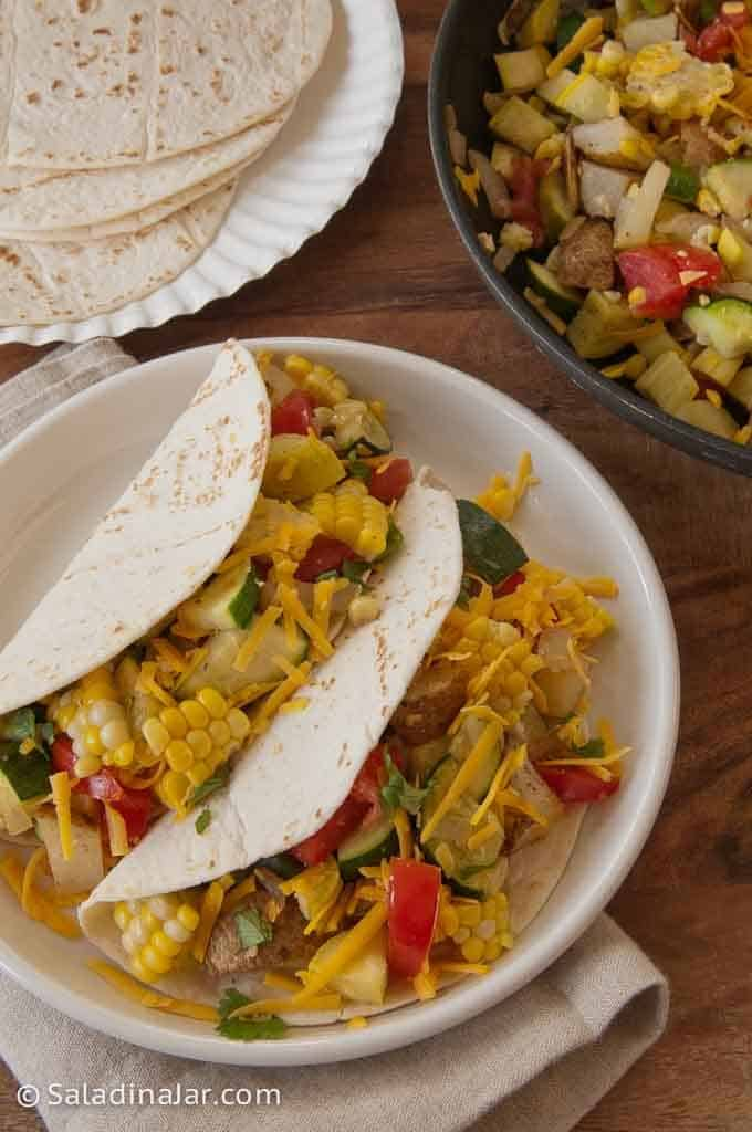 2 Squash and potato soft tacos next to a skillet containing the filling and a plate of soft tortillas.