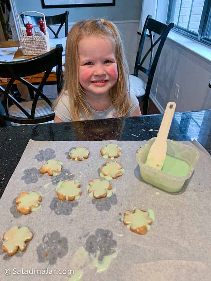 Frosting Shamrock Shortbread Cookies with granddaughter