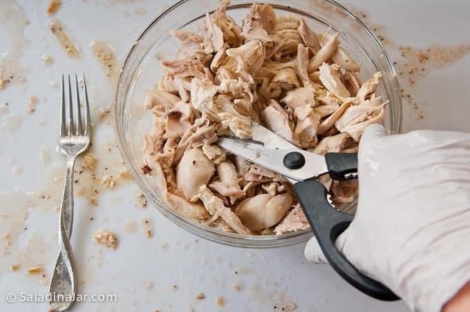 cutting chicken with kitchen scissors