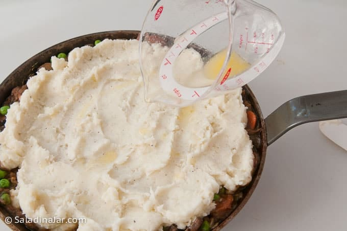 pouring butter over mashed potato layer