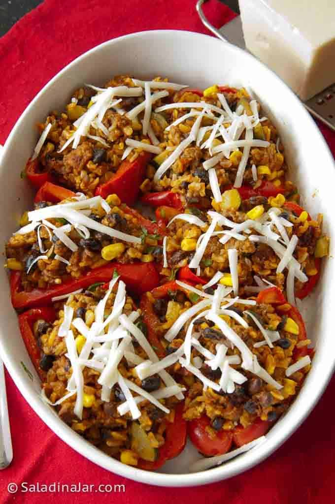 unbaked stuffed peppers with cheese on top