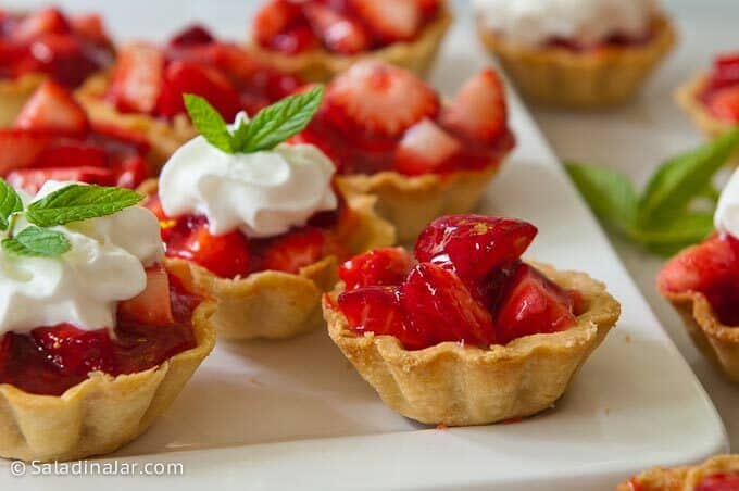 mini strawberry tarts, some with whipped cream on top, ready to eat