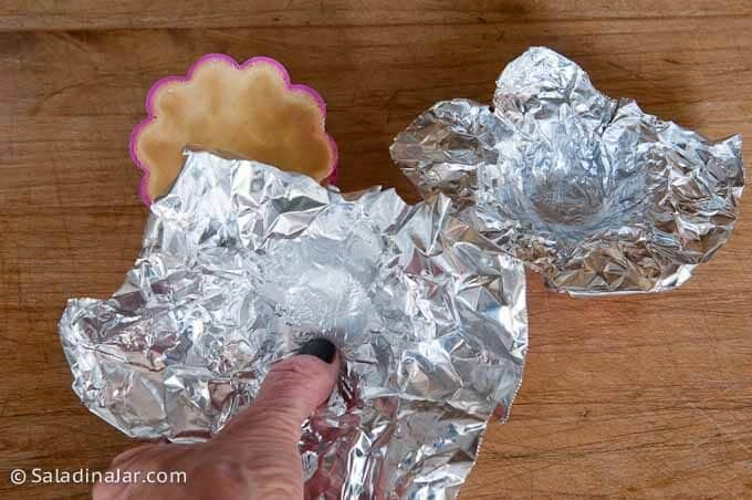 use thumb to press foil inside of tart shell and mold it to the crust