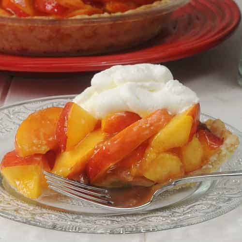 a slice of no-bake nectarine pie with whipped cream on top