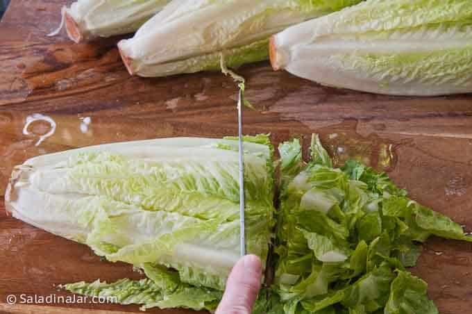 slicing lettuce into small pieces