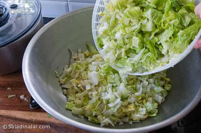 dumping spin-dry lettuce into a large bowl