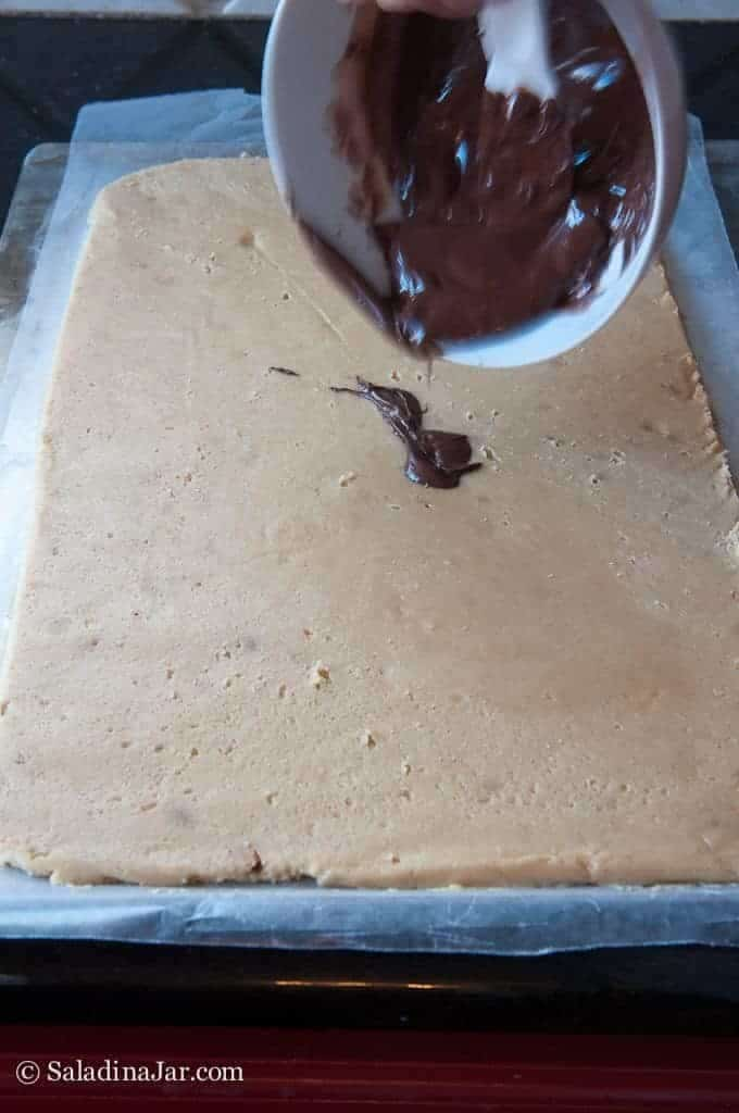 pouring chocolate layer on cookie dough