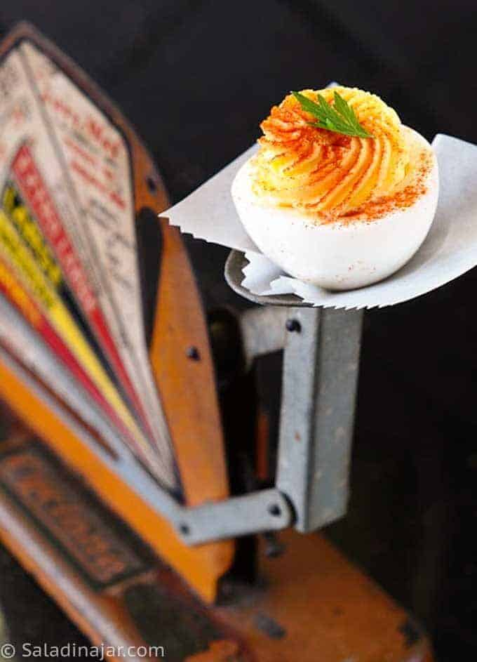 deviled egg displayed on an old-fashioned egg scale