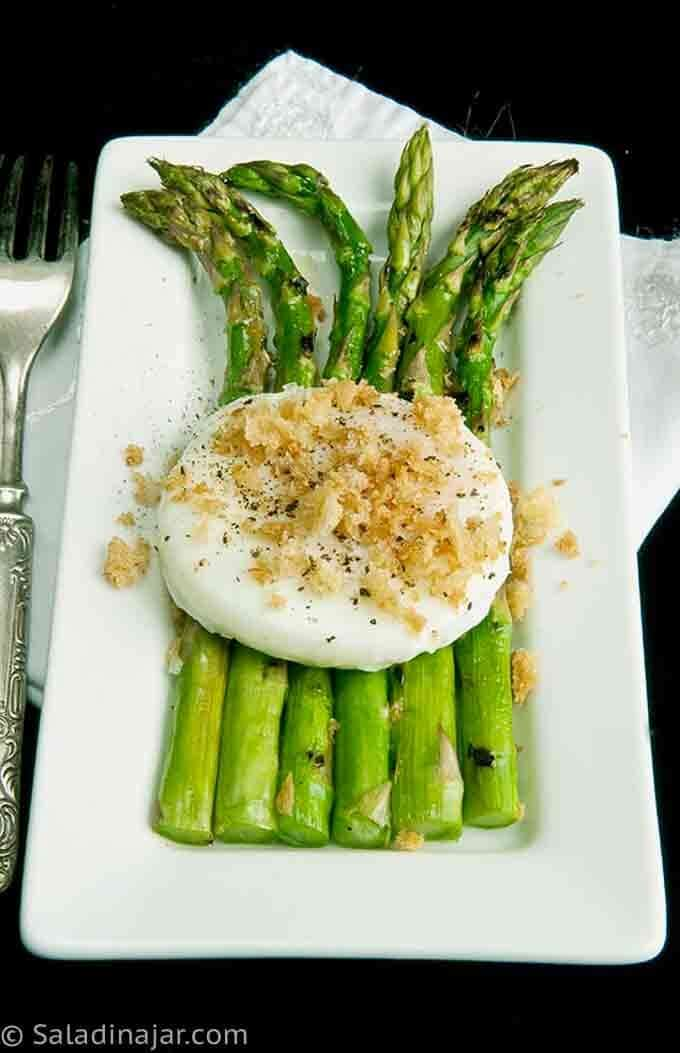 GRILLED ASPARAGUS WITH POACHED EGG AND TOASTY CRUMBLES on a platter