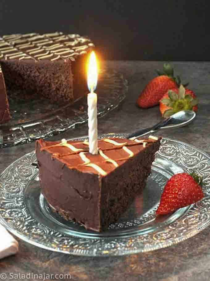 one wedge of GLAZED FUDGE BIRTHDAY CAKE with a candle and strawberry garnish