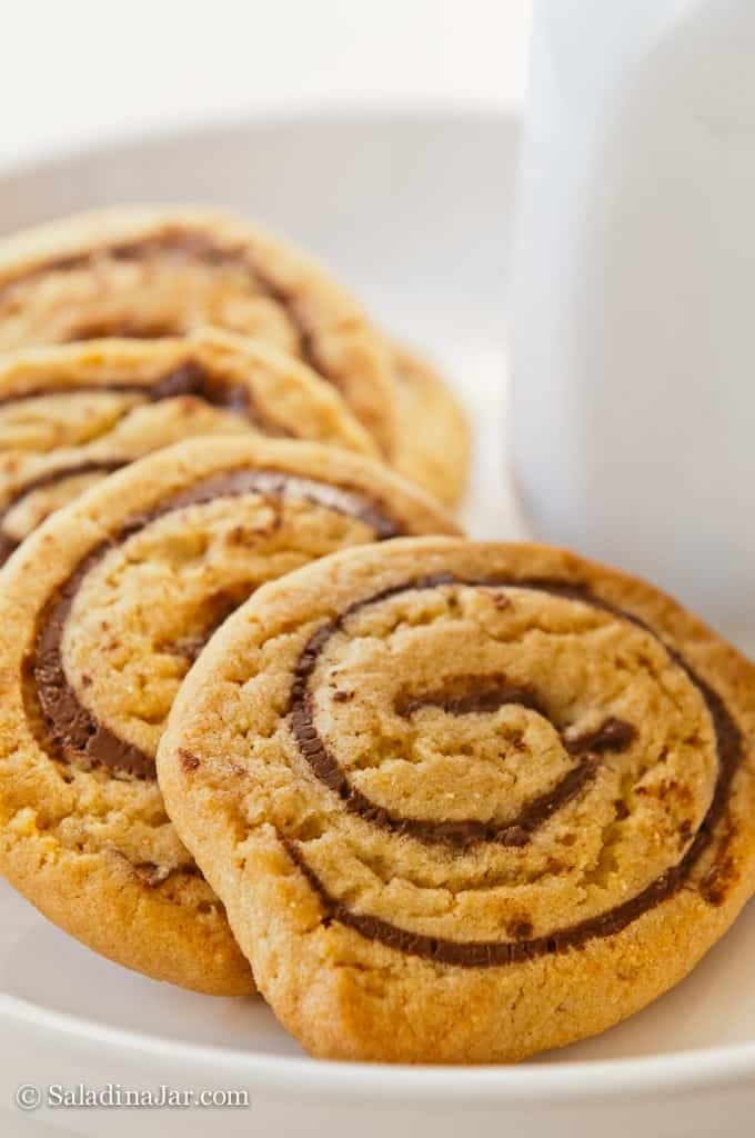 Chocolate peanut butter pinwheel cookies on a plate by milk