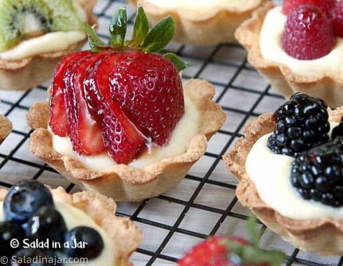 fruit and cream mini tarts on a cooling tray