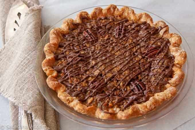 Uncut baked pecan pie with chocolate drizzle