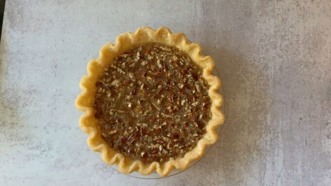 unbaked pecan pie ready to go in the oven