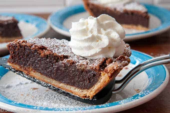 A slice of chocolate fudge pie covered with powdered sugar and whipped cream