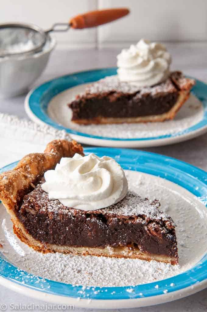 two slices of deep dish fudge pie with pecans topped with whipped cream