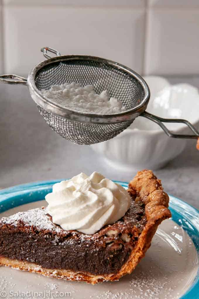 sprinkling homemade fudge pie with powdered sugar using a small sieve