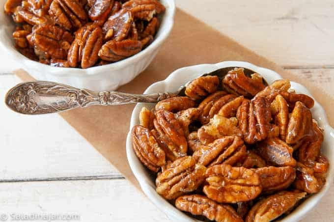 candied pecans in bowls with a spoon
