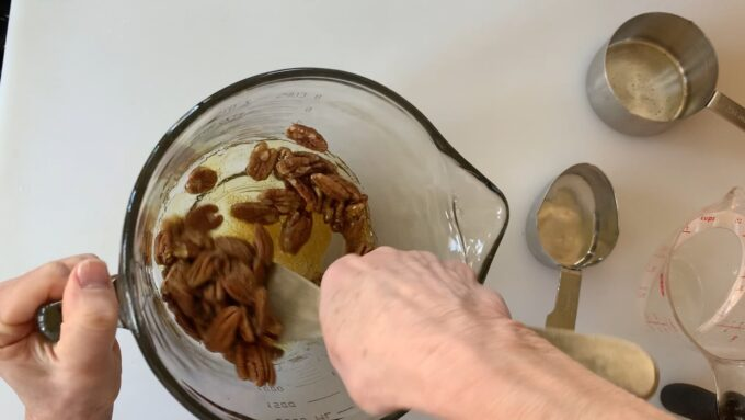 stirring pecans into caramelized sugar