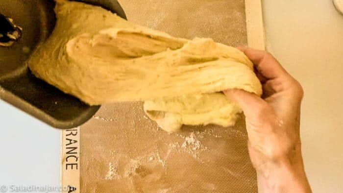 pulling dough out of the bread machine pan onto a floured surface