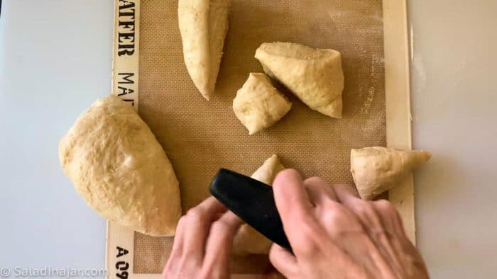 Portioning the dough for rolls with a bench scraper