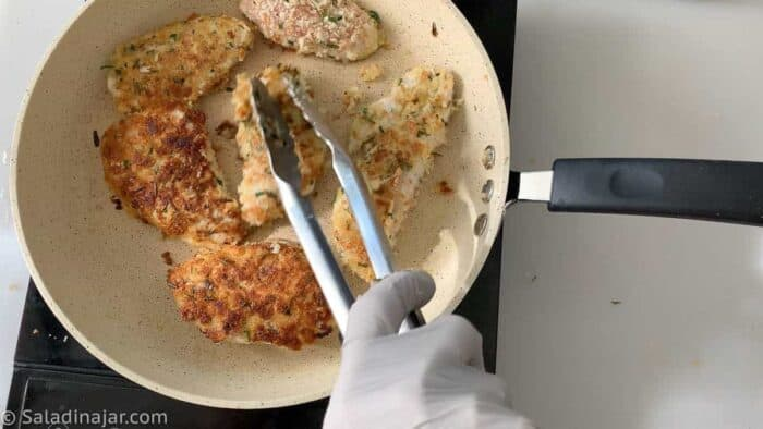 turning chicken filets in skillet