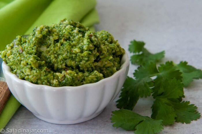 pesto cilantro in a white bowl with fresh cilantro next to it