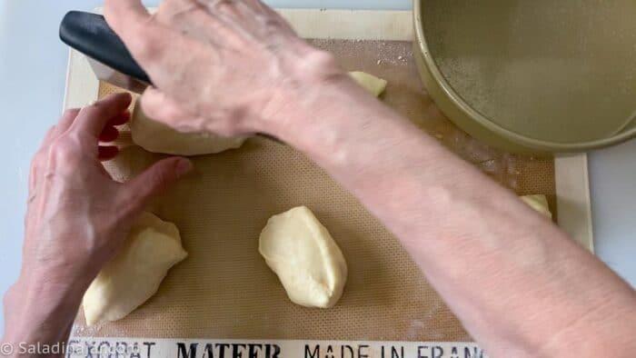 Dividing the original dough ball in two with a bench scraper, then dividing each ball into 8 pieces