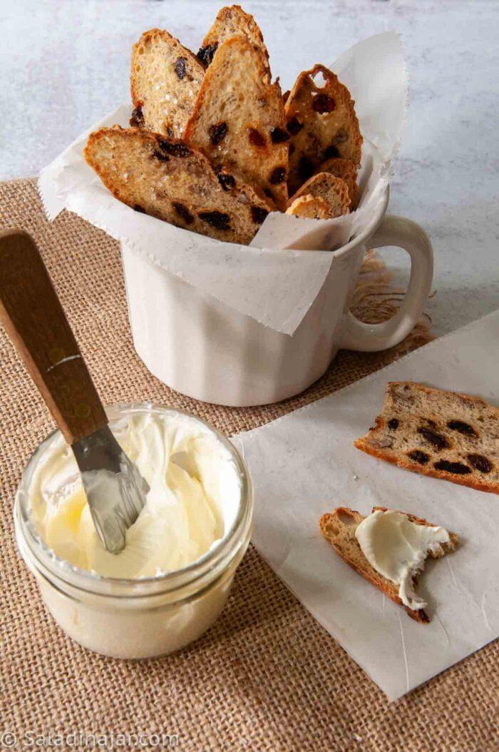 a bowl of homemade crème fraîche next to homemade melba toasts