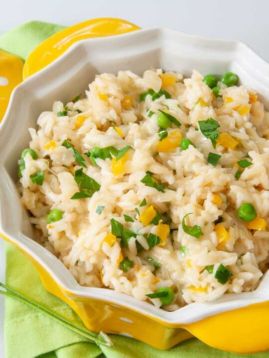 Cheesy Rice in serving bowl with spoon