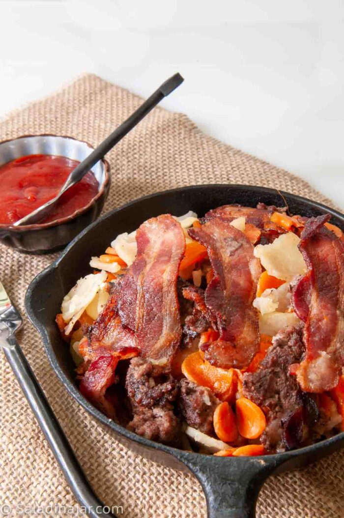 picture of Ground Beef and Potatoes Skillet with Bacon in a black iron skillet with catsup on the side.