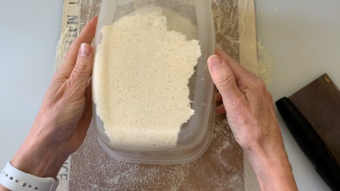 Turning bowl upside down to dump dough onto floured surface.