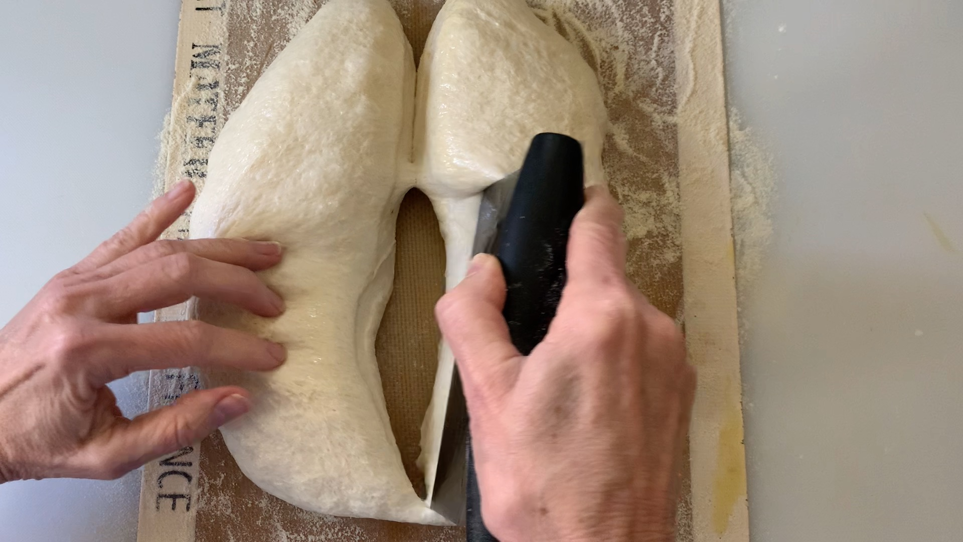 dividing the dough in two pieces with a bench scraper