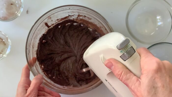 Mixing brownies on low speed with a hand mixer.