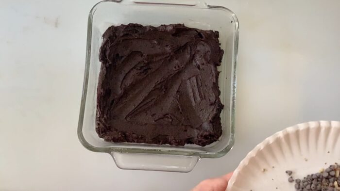 Spreading brownie batter in a glass dish.